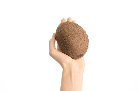 Healthy eating and diet Topic: Human hand holding a ripe brown coconut isolated on white background in studio, first-person view shot