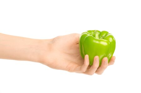 Healthy eating and diet Topic: Human hand holding a green pepper isolated on a white background in the studio shot