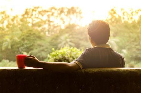 relaxando: Homem novo que relaxa em um jardim com café quente à tarde