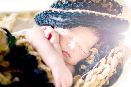 brown background: Newborn baby boy sleeping in basket wearing black  brown hat and blanket isolated in white background