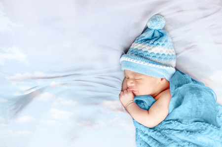Newborn baby boy sleeping on white silk bed floating clouds wearing blue hat and blanket isolated in white background
