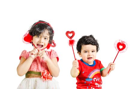 bebes ni�as: Ni�o peque�o y chica posando con el s�mbolo de amor aislados en el fondo blanco Foto de archivo