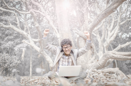 Young business man with white laptop cheering up for success outdoor shoot in winter morning with fallen leaves