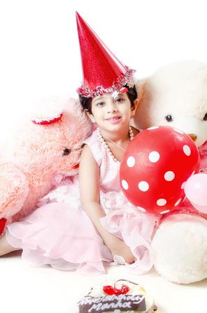 Cute little baby girl Celebrating her birthday surrounded with cake, Teddy bear doll,red balloons & hat isolated in white background