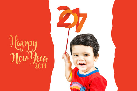 Little cute boy posing with 'Happy new year' & smiling isolated in red & white background