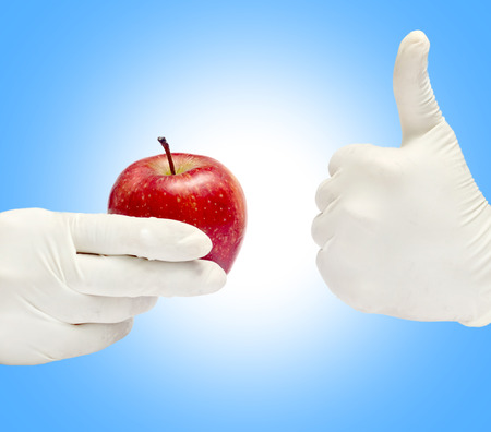Patient education with fresh apple holding in a hand isolated in white background