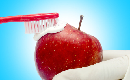 Tooth brushing tecnique with toothpaste  and red apple isolated in white background Standard-Bild