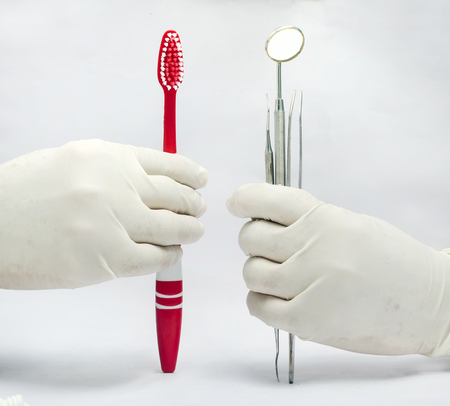 Holding Dental mirror and probe and tweezer amd toothbrush isolated in white background