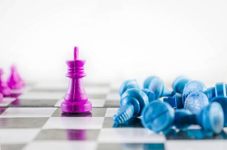Purple king knocked down blue team in a chessboard top view isolated in white background