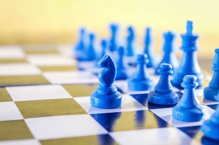 Blue Knight in leading position of a chessboard  isolated in Yellow background Standard-Bild