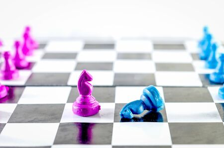 Purple and blue Knight fighting in a  chessboard isolated in white background