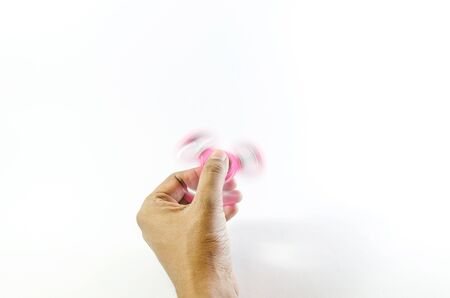 Pink colour fidget spinner holding and moving by a hand isolated in white