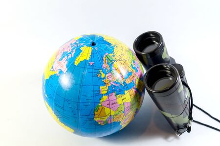 Traveler locating place by a binocular for a travel destination symbolize globe as a world isolated in white Standard-Bild