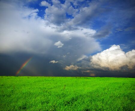 landscape with green grass field, dramatic stormy sky and rainbow Stock Photo