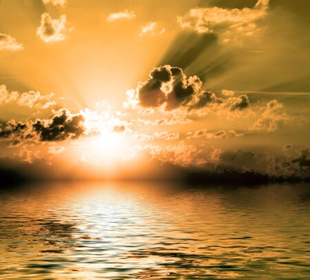 cloudy sunrise with sunbeams blue sky and reflection on water surface Stock Photo