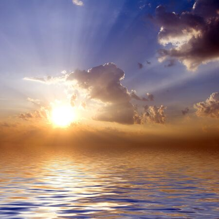 sunrise lake: cloudy sunrise with sunbeams blue sky with reflection in water surface