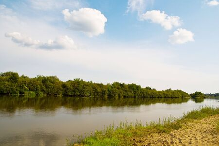 landscape riverside: idillyc rural riverside landscape with green trees,  river, blue sky and fluffy clouds Stock Photo