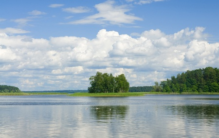 Landscape with grass, trees and fluffy clouds reflecting in water surface of lake Stock Photo