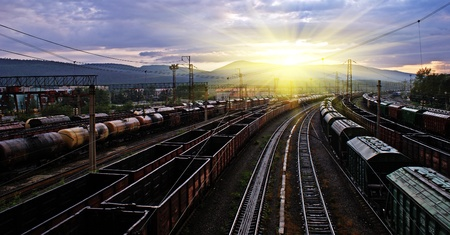 railway station, different trains and wagons at sunset with dramatic sky photo