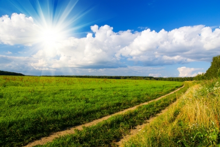idilic rural landscape with green grass field, blue skywith sun, fluffy clouds and road in sunset light Stock Photo