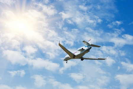Private business jet airplane flying on blue sky, sun and clouds background