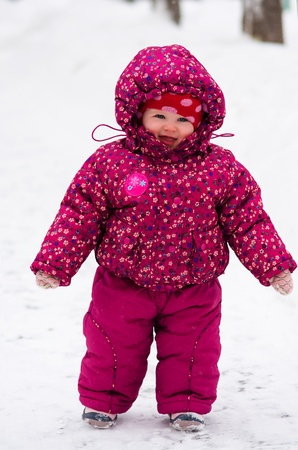 little toddler girl in winter clothes walks by snow at showfall