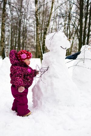 toddler baby child with snowman in winter park photo