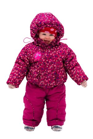little toddler girl in winter clothes walks by snow isolated over white  Stock Photo