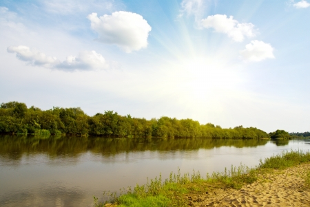 riverside landscape: idillyc rural riverside landscape with green trees,  river, blue sky and fluffy clouds Stock Photo