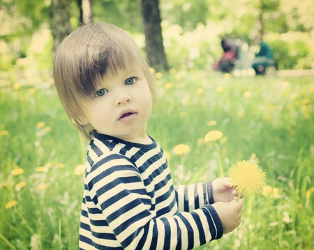 Little toddler girl outdoor and holding yellow flower dandelion retro toned photo