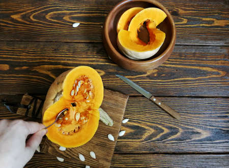 sliced pumpkin with a knife on a wooden Board and the old background