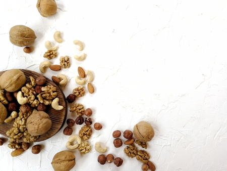 different nuts, peeled and in-shell on textured background
