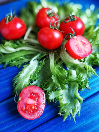 red cherry tomatoes with green lettuce leaves on blue background Stock Photo