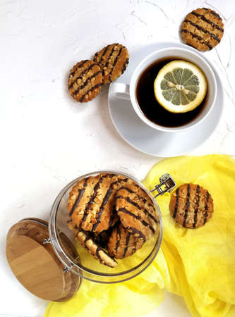 cookies polished with chocolate and peanut pieces in a glass jar with a wooden lid on a light table a Cup of tea with a slice of lemon and a yellow runner.