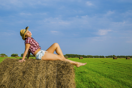 brunette girl with short hair in a red plaid shirt, denim short shorts and cowboy hat in the field at the haystack with red apples Reklamní fotografie - 101442107