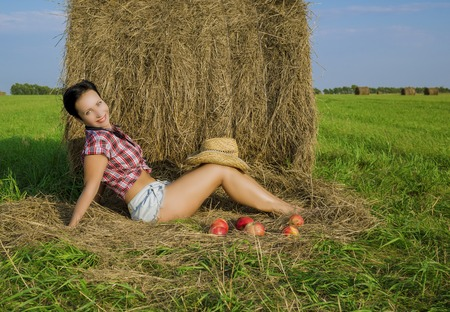 brunette girl with short hair in a red plaid shirt, denim short shorts and cowboy hat in the field at the haystack with red apples Reklamní fotografie - 101441990