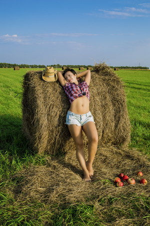 brunette girl with short hair in a red plaid shirt, denim short shorts and cowboy hat in the field at the haystack with red apples