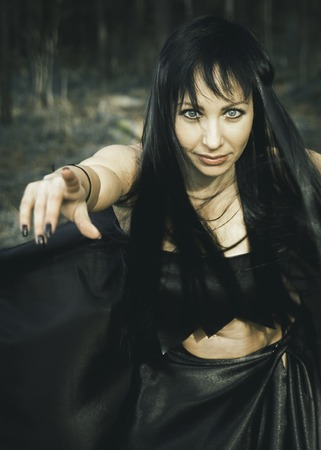 girl witch brunette in black leather top and long black skirt with long black hair in autumn forest on all saints day, concept-Halloween