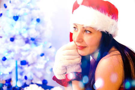 brunette girl with long hair in a red gnome suit and a striped cap at a white Christmas tree decorated with blue balls on a white background, isolate