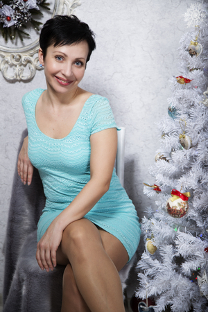 brunette girl with short hair in a short blue dress with heels on a fur plaid blue mink at the white Christmas tree with toys and gifts for Christmas. Stock Photo