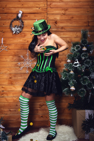 brunette girl in an elf costume in a green corset and short skirt in green and white striped Golf in a green cylinder with a pot of gold of St. Patrick's day for the new year