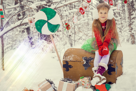 a red-haired girl with long hair in a lush skirt and a green cloak with lace, in the costume of dwarf assistant Santa Claus in the winter forest with huge candy, a chest of gifts collects in a basket Christmas balls