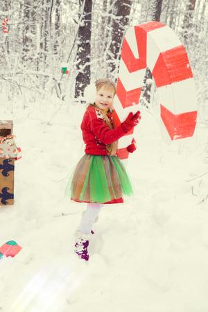 巨大なキャンディーと冬の森の中で小人助手サンタクロースの衣装で、緑豊かなスカートとレースと緑のマントに長い髪を持つ小さな赤い髪の女の子は、贈り物の胸はバスケットクリスマスボールに集まる 写真素材 - 107431683