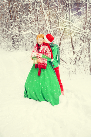 young couple, husband and wife are walking in costumes of flowers typical of the elves of Santa's helpers in a winter forest under the snow with a chest full of gifts and a giant candy