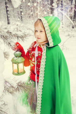 a little red-haired girl with long hair in a lush skirt and a green cloak with lace, in the costume of dwarf assistant Santa Claus in the winter forest with huge candy, a chest of gifts collects in a basket Christmas balls 写真素材