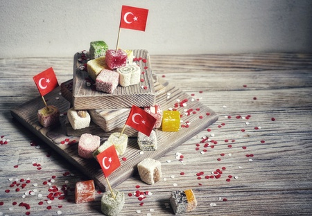 various national Oriental sweets, with paper flags of Turkey, Turkish delight on a wooden white brushed stand and on a white brushed background, horizontal, the concept of the independence day of Turkey.