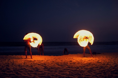High Skill Man playing fireworks by spinning wood pole with fuel oil and fire, circle around as ring of fire on beach along ocean in tropical island, long high exposure blur movement.