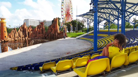 lifestyle, girl in yellow t-shirt, autistic child sitting on the podium in front of the Park with rides and covers his ears with his hands.