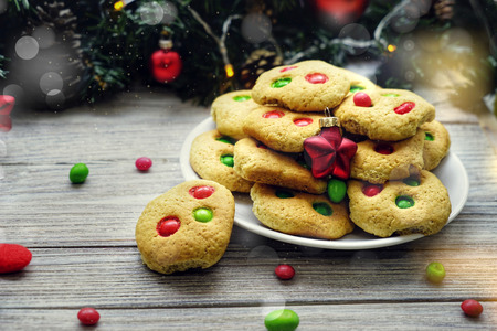Shortbread cookies with multi colored candy and chocolate chips, served with glass of milk, square format.