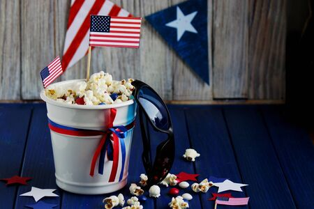 Patriotic popcorn on July 4 in a white bucket with the American flag on a blue wooden background.The US independence day.